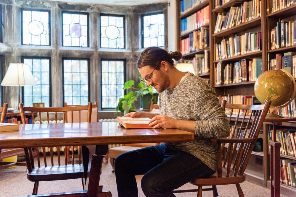 Man reading a book in the library at St. Margaret's House.